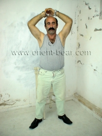 In this turkish gay video he wears handcuffs at the beginning and is dressed in street clothes.