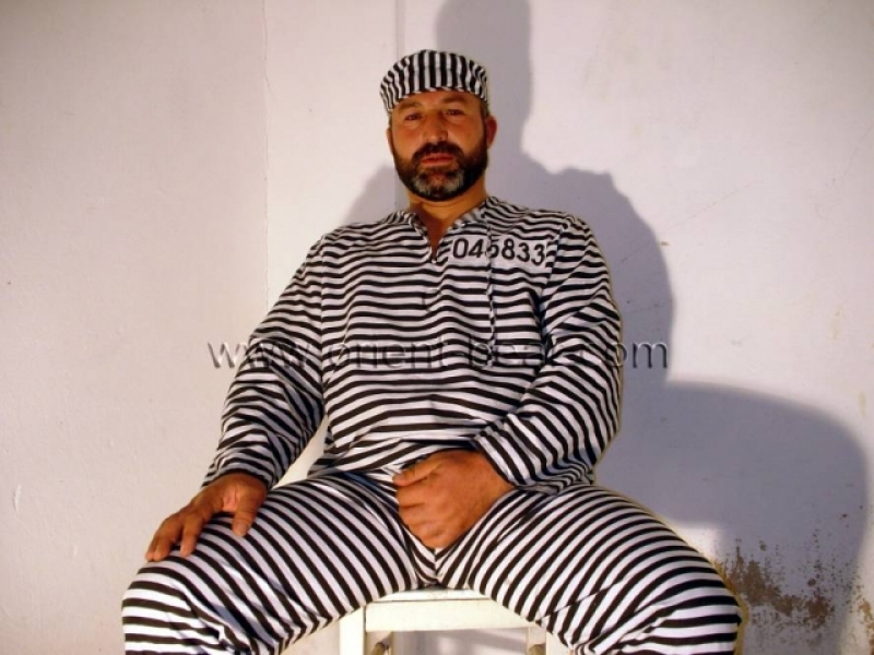 Ercan - a strong older turkish bear in prison clothes strips naked and jerks his big very hard cock in a turkish gay video. (id111)