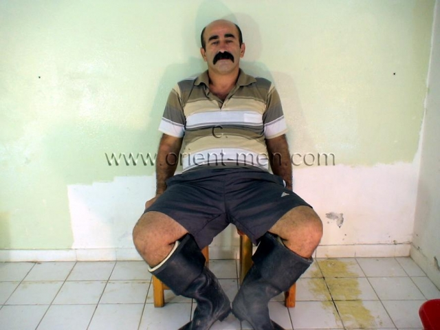 A heavily haired turkish bear in rubber boots and a thick mustache. His body is hairy from top to bottom like a monkey. His cock has a normal size, gets pretty hard and he has a bush. He is a construction worker and sweat the whole day, so he is a little red in the crotch. His face is very masculine with his thick mustache.