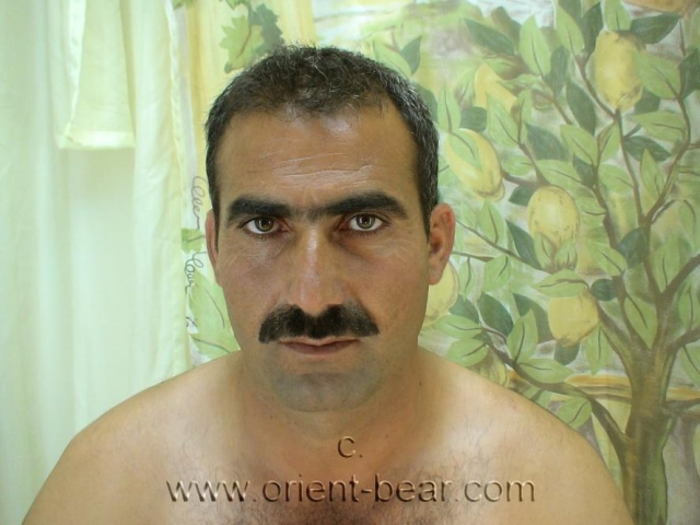 Tarek D. a big naked kurdish man with a long skinny cock and a long hanging scrotum and a huge black bush. He is an ex policeman with a very erotic face with a horny mustache. In this gay video, he already sits naked in the studio on a bench. When he wank, he kneels before one on the floor in front of the bank.