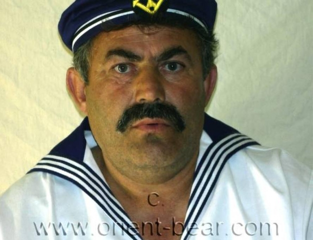 go to this turkish gay photo series. A older turkish man with a very hard cock and a horny hairy ass crack as a sailor in a turkish gay video. He has a very strong, normally hairy body. His cock is very hard, has a big cockhead and he has a bush. In this turkish gay video he plays a sailor in uniform. He is already naked at the beginning of the video below. He keeps the jacket and the hat on throughout the video. He jerks while sitting and standing, while the camera shows his hairy ass crack from below.