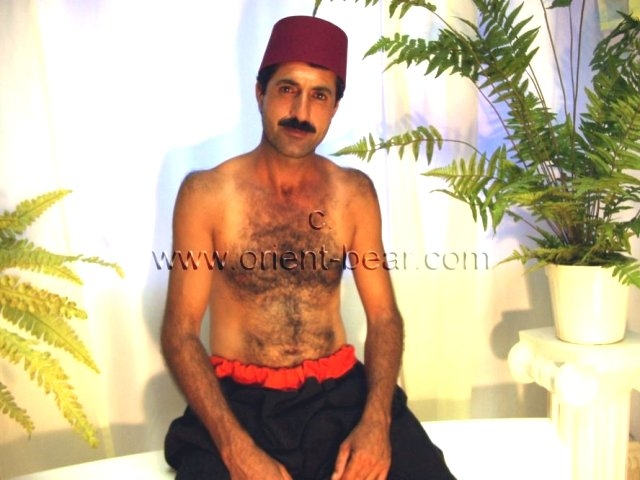 go to this turkish gay photo series. In this turkish gay video you see a tall kurdish man with a huge cock and he shows his hairy ass in doggy style.  His body is hairy, very tall and slim. His huge cock is long and very hard and he has a big cock head. He totally shaved his bush. In this turkish gay video he is sitting on a bench in the studio in old farm clothes in salvar and fez. He plays with his huge cock and strips naked.