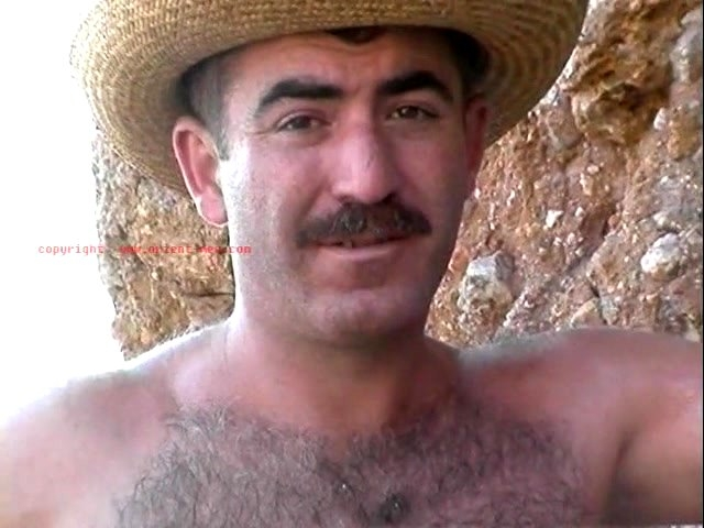 go to this turkish gay photo series. A naked very hairy turkish bear with very big balls and a fully hairy butt jerking off the beach in an turkish outdoor gay video. The video plays by the sea you can hear the waves. He takes off his bathing shorts and starts jerking off. His cock is a normal size, but is pretty thick and has a big cock head. He has fur as body hair and he has totally shaved his bush. That looks very cool. He also shows his very hairy butt, while you can see well his clean-shaven ass crack with hole. In his cumshot he sits on a stone and his cum lands on his thigh.