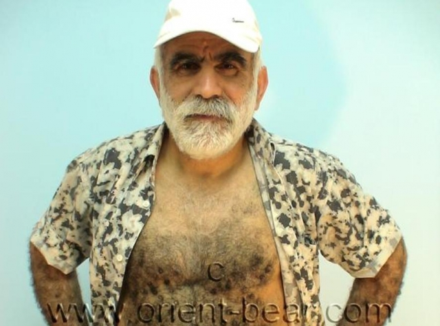 go to this turkish gay photo series. An older turkish man with a full hairy body and a very big cock jerking off on a rubber boot in a turkish gay video. His body is hairy from top to bottom. His butt has plump firm totally hairy ass cheeks. Stroking his butt is a crazy feeling. His cock is nice and long and he has a big cockhead. His pubic hair he trimmed something in this video. In this turkish gay video, he strips naked and then stands naked in rubber boots. go to this photo series