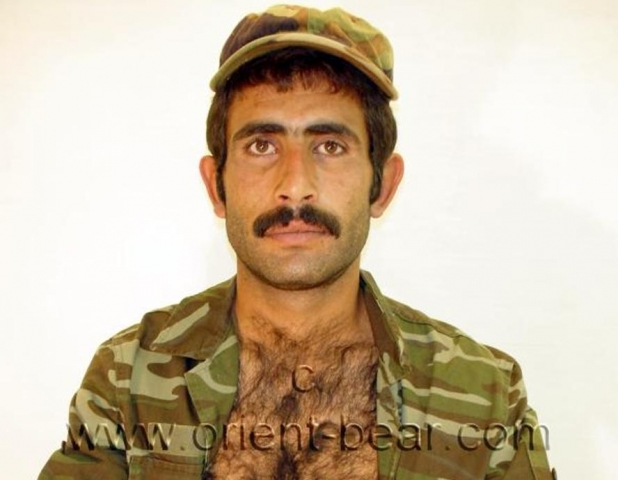 A naked iraqi kurd with a horny hairy body and a big very hard cock. His body has a perfect hairy figure. His cock is pretty big with a horny cockhead and a full bush. He has an oriental face with a horny mustache. The camera also shows his plump hairy ass cheeks from below. In this gay video he plays a soldier.